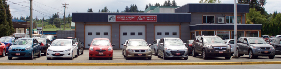 Row of pre-owned cars and suvs in front of a 3-bay garage. Auto sales office on right side.